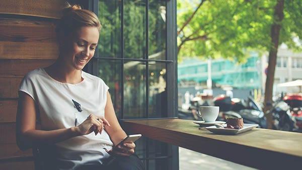 Chica en rede sociales en smartphone desde una cafetería